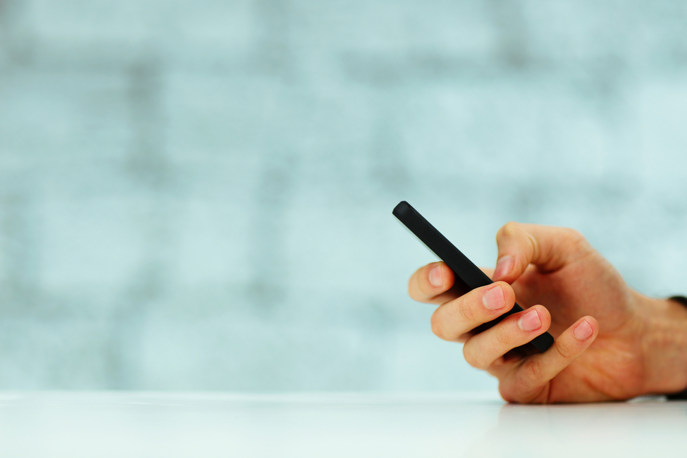 Closeup image of a male hand typing on smartphone